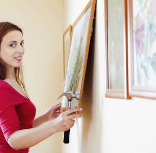 Woman framing and hanging pictures | Hiscox Cover Stories