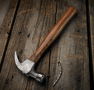 Hammer and bent nail shot on a rustic barn board surface