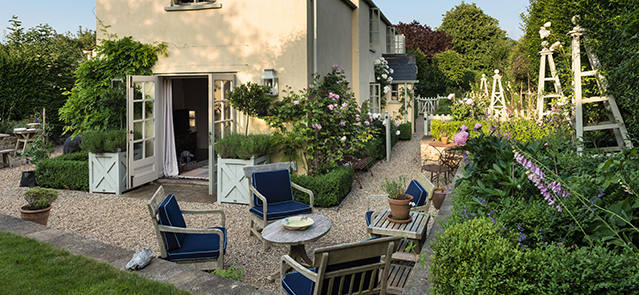 Outdoor wooden furniture in garden of english country cottage