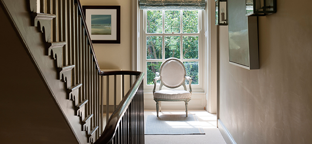 Round back French armchair on staircase landing with large paned window