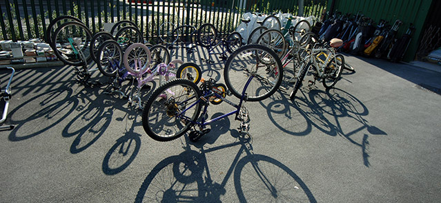 Bicycles casting long shadows in a recycling centre in Bideford, North Devon.. Image shot 2007. Exact date unknown.
