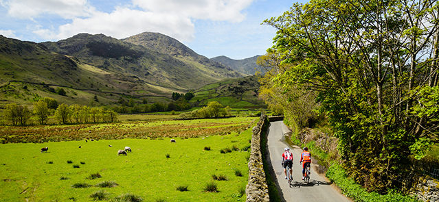 Cyclists in Little Langdale in the English Lake District with the Coniston Fells behind