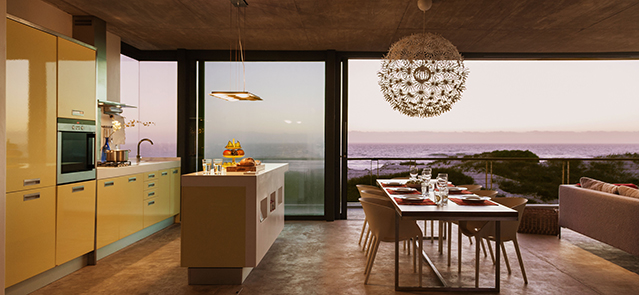 Modern kitchen and dining room overlooking ocean at sunset. Image shot 2013. Exact date unknown.
