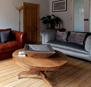 Brown leather and grey silk sofas with circular side table in living room of Macclesfield townhouse, Cheshire, England, UK