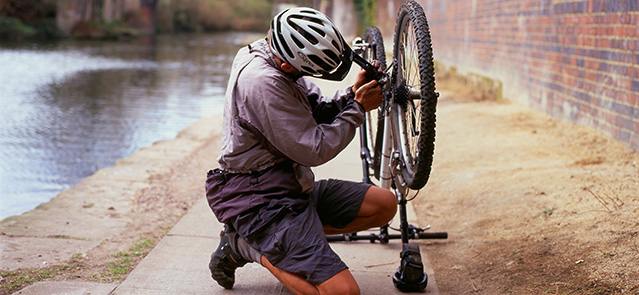 A cyclist  wearing a cycling helmet mending his bicycle on Regents Canal path near Camden Lock London England UK KATHY DEWITT. Image shot 2006. Exact date unknown.