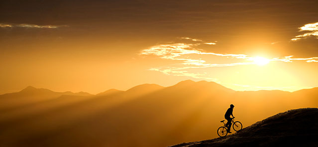 Mountain biker rides up a hill at sunset. This one is in Arizona, just west of Tucson.