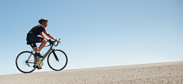 Low angle image of a male cyclist riding on a flat road against blue sky. Man cycling up hill on open road.