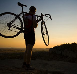 Man standing on the edge of a cliff holding a bicycle at sunset.