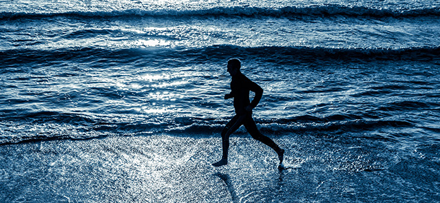 Man running on beach at sunrise