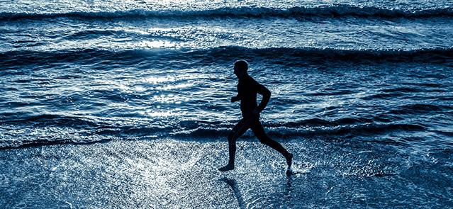 Man running on beach at sunrise