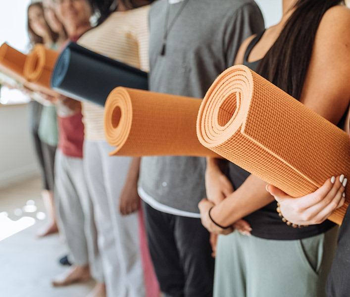 A group of people holding their yoga mats in the studio