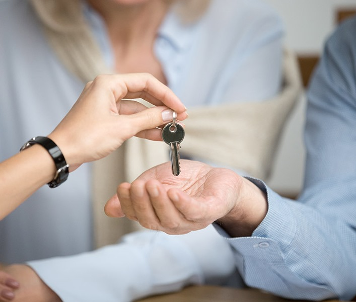 An estate agent handing a key over to a new tenant